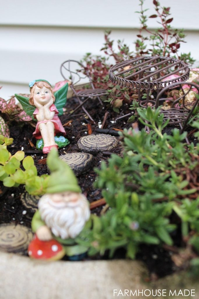 This DIY Fairy Garden made from a salvaged bird bath is simply adorable! I love the whimsical chairs and hedgehog so much! My kids would love this!