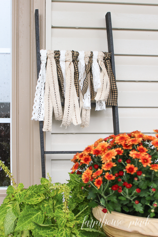 This adorable farmhouse style porch is easy to create, and the ribbon ladder adds a sweet touch!