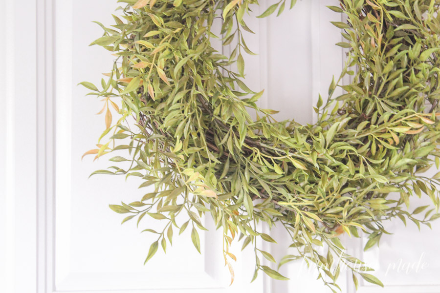 Do you know you can save so much money by making this easy greenery wreath? In the store, these things are crazy expensive! Wreaths look perfect for hanging anywhere, so get 5 minutes and a friend to make this quick and easy greenery wreath!
