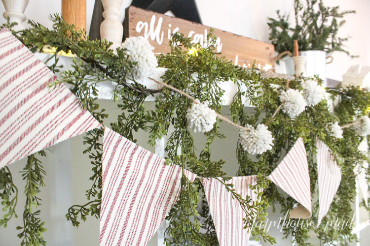 A perfectly minimal farmhouse Christmas mantel with a hand painted wood sign, and adorable vintage candlesticks, pom pom garland and red ticking bunting!