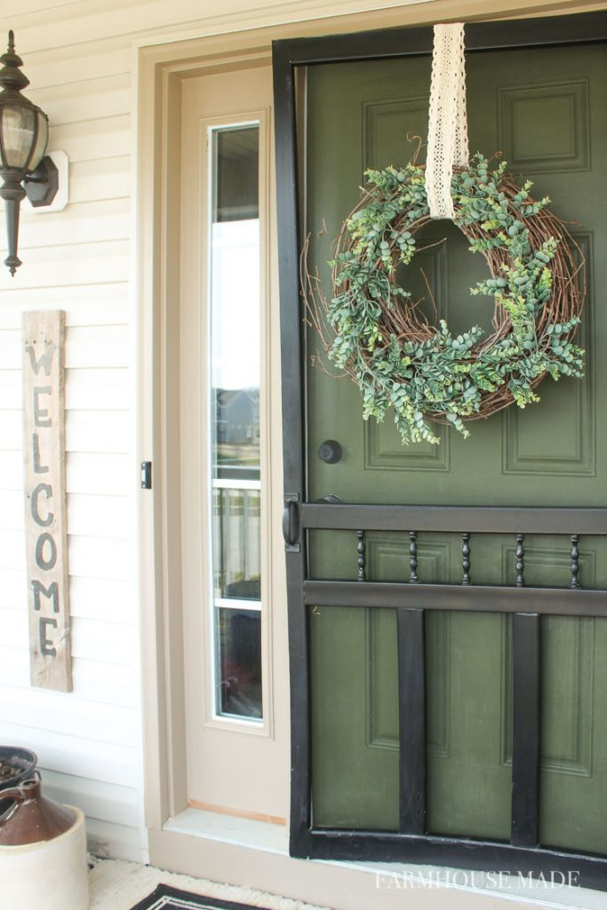 Spring has sprung on my front door! The spring wreath welcomes you home, while it hangs on this farmhouse screen door! Eucalyptus garland and a misshapen grapevine garland wreath are a perfect pair. #wreath #springwreath #diywreath