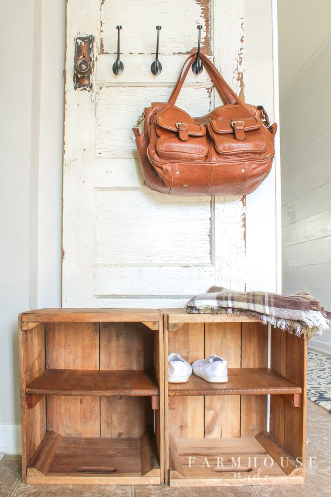 Shoe storage cubbies made from 2 salvaged apple bushel boxes with an antique door