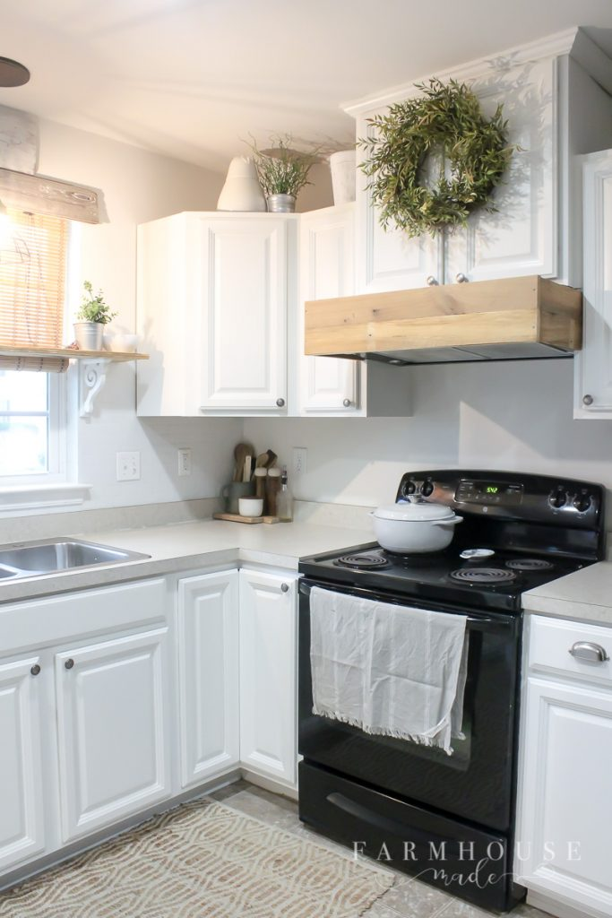 Rustic vent hood over black stove, in white farmhouse kitchen with painted cabinets
