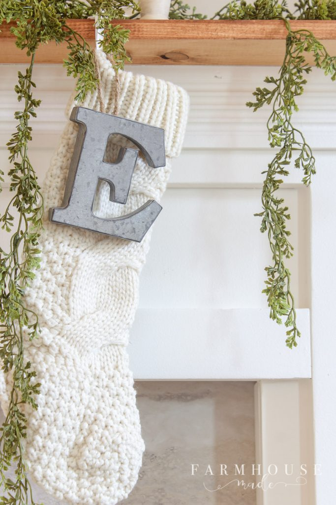 galvanized metal letters hang on cable knit christmas stockings from diy faux fireplace mantle